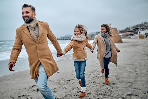Ritratto di una giovane coppia di sposi e la loro figlia carina che si divertono sulla spiaggia in inverno indossando vestiti caldi e sciarpe in inverno.
