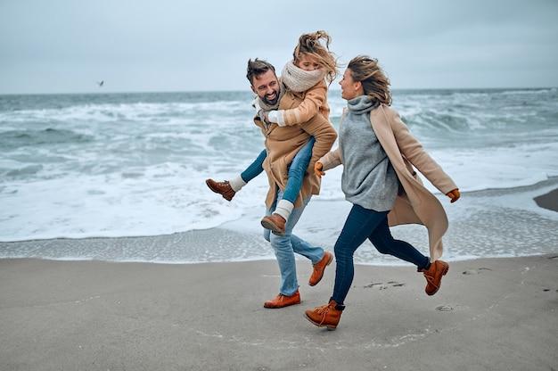 Ritratto di una giovane coppia di sposi e la loro figlia carina che si divertono sulla spiaggia in inverno.