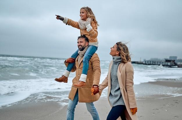 Ritratto di una giovane coppia sposata e della loro figlia carina che si divertono sulla spiaggia in inverno.