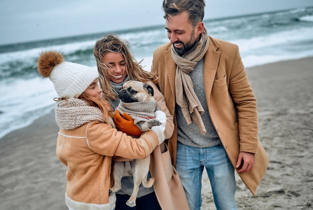 Ritratto di una giovane coppia sposata e della loro figlia carina che si divertono con un cane sulla spiaggia in inverno indossando vestiti caldi e sciarpe nella stagione fredda.