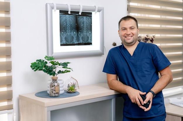 Ritratto di giovane medico in camice in piedi vicino a lavagna luminosa con risultati di risonanza magnetica. ritratto di medico maschio nella moderna sala medica.