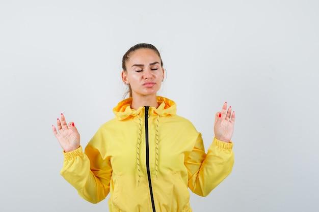 Ritratto di giovane meditando in giacca gialla e guardando la vista frontale rilassata