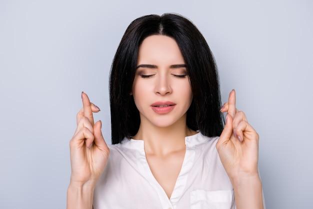 Ritratto di giovane donna di mentalità in camicia bianca con gli occhi chiusi e le mani incrociate in attesa di successo
