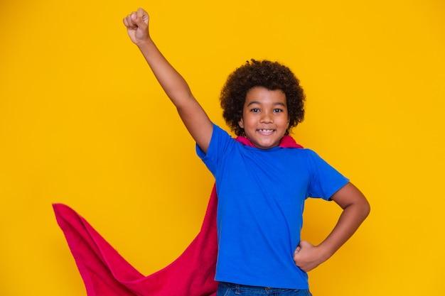 Ritratto di un giovane ragazzo di razza mista vestito da supereroe. bambino nero in costume da super eroe. il vincitore e il concetto di successo.