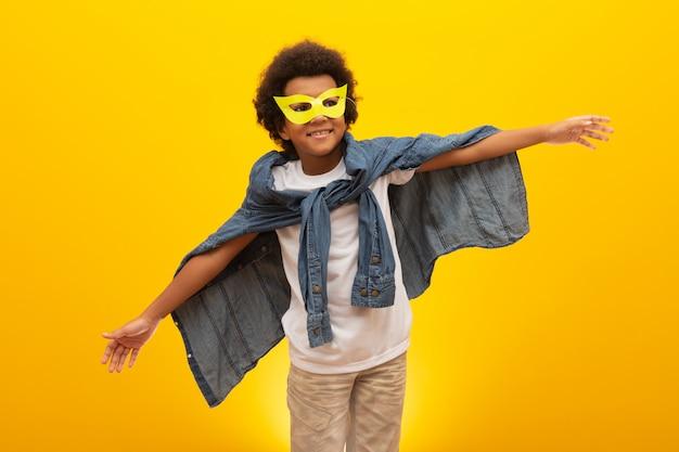 Ritratto di un giovane ragazzo di razza mista vestito da supereroe. bambino nero in costume da supereroe. il vincitore e il successo