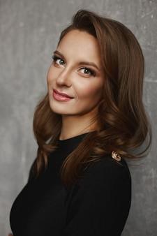 Ritratto di una ragazza giovane modello con trucco luminoso e una pelle perfetta in un vestito nero