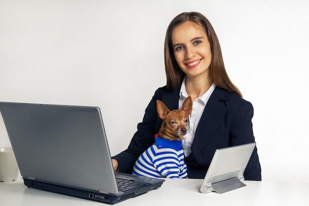 Ritratto di giovane donna moderna che cerca di lavorare su laptop con un cane di piccola taglia in braccio al chiuso