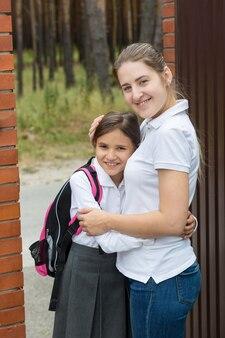 Ritratto di giovane madre che abbraccia sua figlia prima di vederla andare a scuola