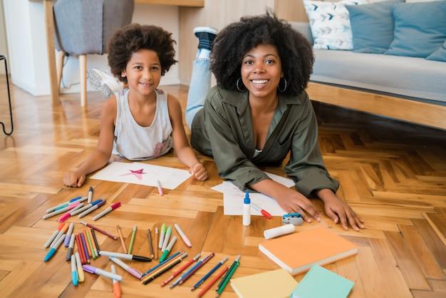 Ritratto di giovane madre e figlio di disegno con matite colorate sul pavimento caldo a casa