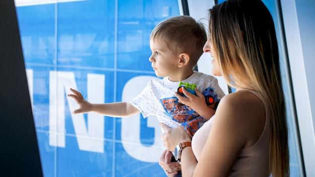 Ritratto di giovane madre msiling che abbraccia il suo piccolo figlio e guarda attraverso la finestra nel terminal dell'aeroporto.