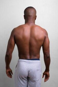 Ritratto di giovane uomo muscoloso africano a torso nudo su bianco