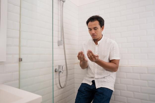 Ritratto di giovane uomo musulmano che prega dopo eseguire l'abluzione (wudhu) in bagno