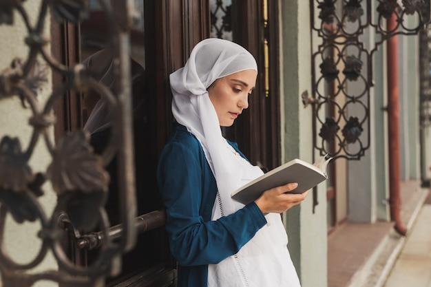 Ritratto di giovane donna musulmana che indossa il libro di lettura hijab all'aperto