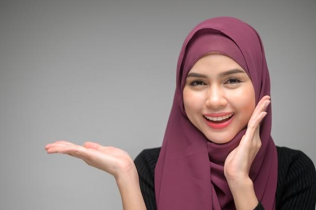 Un ritratto di giovane donna musulmana su sfondo bianco studio
