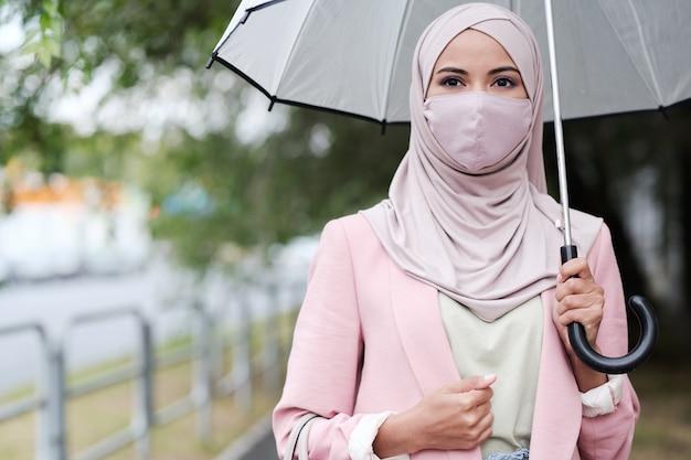 Ritratto di giovane donna musulmana con la bocca coperta tenendo l'ombrello mentre si cammina sotto la pioggia