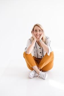 Ritratto di giovane bella donna con gli occhiali sorridente e seduto sul pavimento con le gambe incrociate isolato sopra il muro bianco