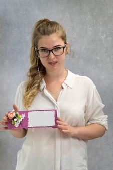 Ritratto di giovane infermiera in bicchieri con buono regalo in mano. certificato vuoto. copia spazio. modello.