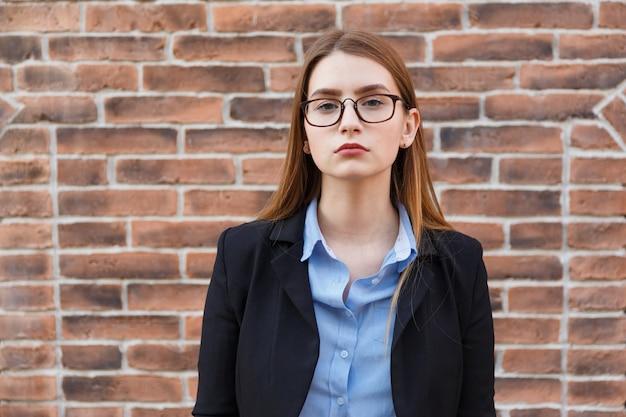 Ritratto di giovane impiegato donna in tuta e occhiali da vista sul muro di mattoni