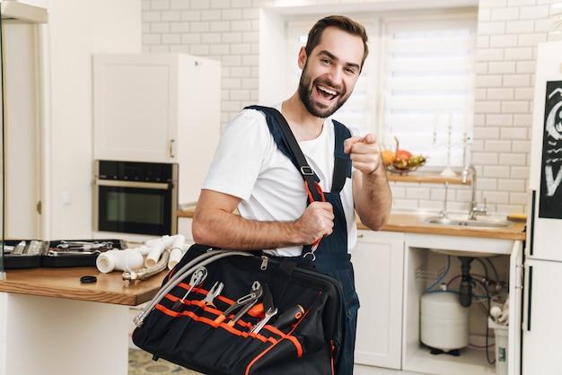 Il ritratto di giovane idraulico positivo ottimista dell'uomo lavora in uniforme all'interno che tiene la borsa con l'attrezzatura che indica voi.