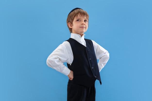 Ritratto di un giovane ragazzo ebreo ortodosso isolato sulla parete blu dello studio
