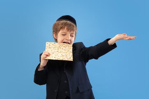 Ritratto di un giovane ragazzo ebreo ortodosso isolato sulla parete blu dello studio.