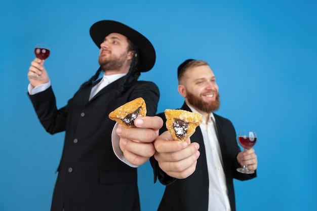 Ritratto di un giovane ebreo ortodosso uomini isolati su sfondo blu per studio, incontrando la pasqua ebraica, mangiando le orecchie di aman con il vino