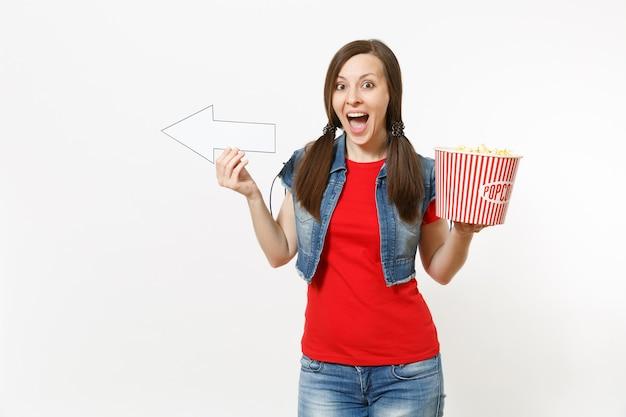 Ritratto di giovane donna felicissima in abiti casual che guarda film, tenendo il secchio di popcorn, puntando la freccia bianca da parte sullo spazio della copia isolato su sfondo bianco. emozioni nel concetto di cinema.