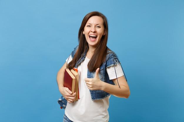 Ritratto di giovane studentessa felicissima con la bocca aperta con lo zaino che mostra pollice in su e tiene i libri di scuola isolati su sfondo blu. istruzione nel concetto di college universitario di liceo.