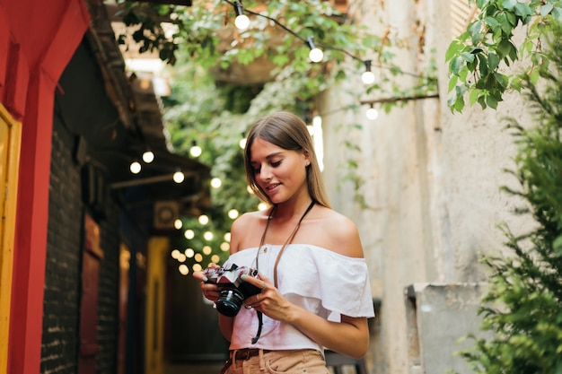 Ritratto di giovane donna appassionata turistica con retro macchina fotografica nelle sue mani mentre posa alla vecchia architettura urbana. scopri nuovi posti