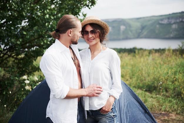 Ritratto di giovani, un ragazzo e una donna, turisti che stanno in piedi vicino a una tenda e si ritrovano a riposare nella natura