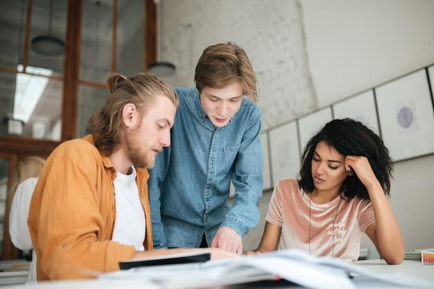 Ritratto di giovani che discutono minuziosamente qualcosa in ufficio