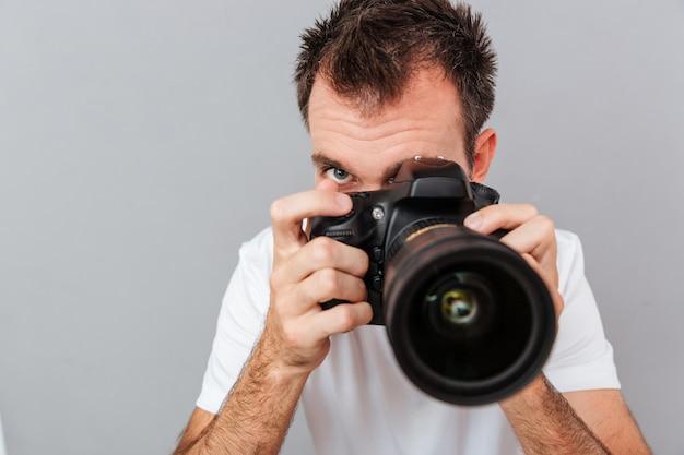Ritratto di un giovane fotografo con fotocamera isolata su sfondo grigio