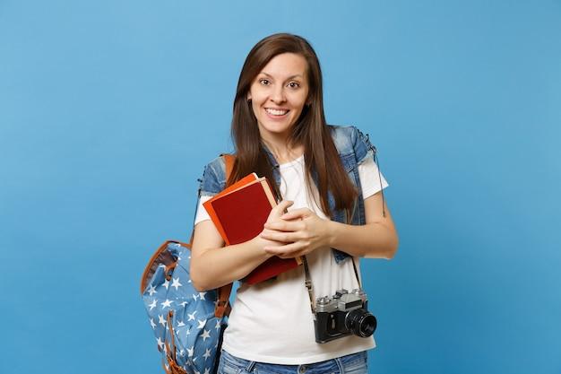 Ritratto di giovane studentessa piacevole con zaino e macchina fotografica d'epoca retrò sul collo che tiene libri di scuola isolati su sfondo blu. istruzione nel concetto di college universitario di liceo.