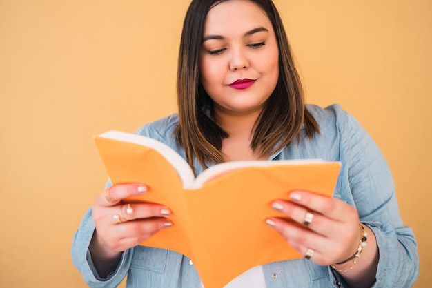 Ritratto di giovane donna plus size godendo del tempo libero e leggendo un libro in piedi sul giallo. concetto di stile di vita.