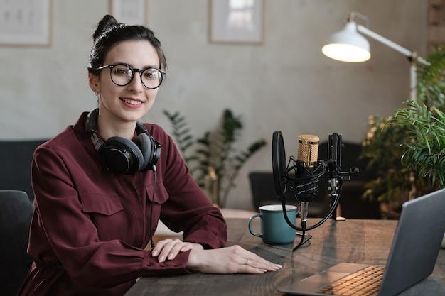 Ritratto di giovane podcaster in cuffia che sorride alla telecamera mentre è seduto al tavolo davanti al laptop e lavora in studio radiofonico