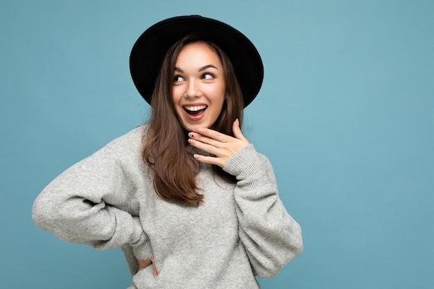 Ritratto di giovane bella donna castana sorpresa felice positiva con emozioni sincere che indossa il tiro grigio alla moda