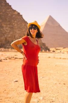 Ritratto di una giovane donna incinta in abito rosso presso la piramide di cheope, la piramide più grande. le piramidi di giza il più antico monumento funerario del mondo. nella città del cairo, in egitto