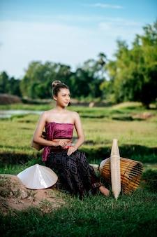 Ritratto giovane bella donna asiatica in bellissimi abiti tradizionali tailandesi al campo di riso, seduta vicino all'attrezzatura da pesca