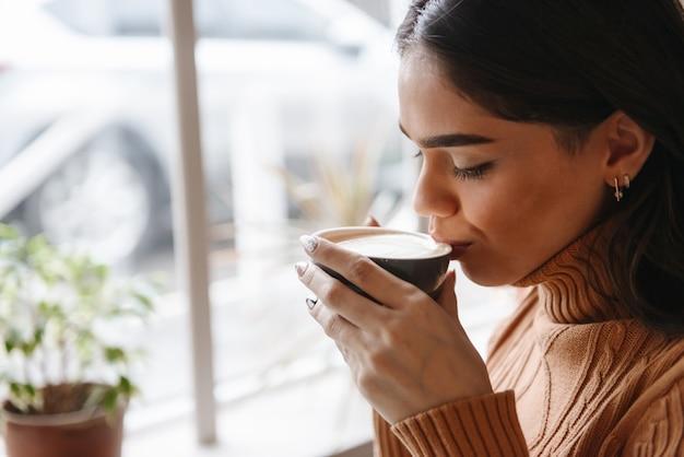 Ritratto di una giovane donna abbastanza bella seduta in un bar al chiuso a bere il caffè.