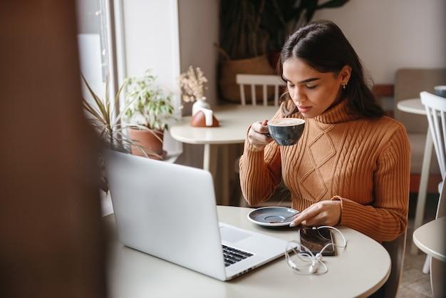Ritratto di una giovane donna abbastanza bella seduta in un bar al chiuso utilizzando computer portatile bere caffè.
