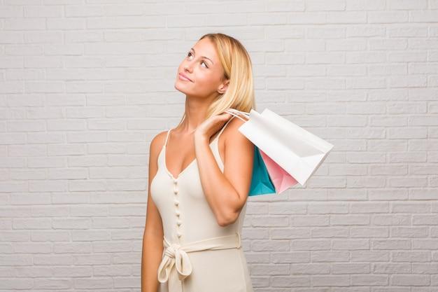 Ritratto di giovane donna bella bionda contro un muro di mattoni alzando lo sguardo, pensando a qualcosa di divertente e avendo un'idea, concetto di immaginazione, felice ed emozionato. in possesso di borse della spesa.