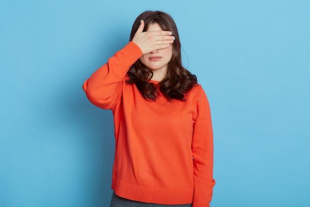 Ritratto di giovane donna spaventata piuttosto caucasica che copre gli occhi con le mani in piedi contro il blu