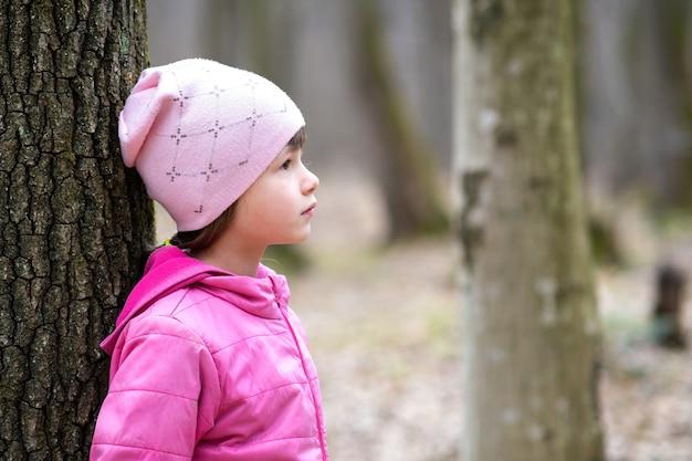 Ritratto di giovane ragazza graziosa del bambino che indossa giacca rosa e cappuccio appoggiato a un albero nella foresta godendo calda giornata di sole in primavera all'aperto.