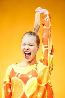 Ritratto di giovane ragazza urlante piuttosto divertente che indossa una felpa stampata arancione