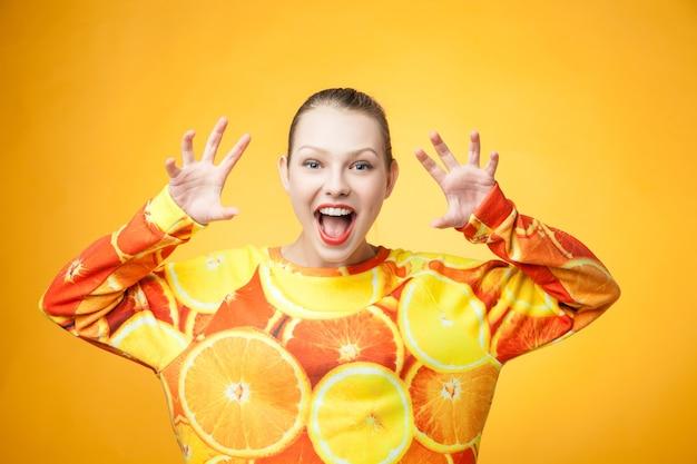 Ritratto di giovane ragazza sorridente piuttosto divertente che indossa una felpa stampata arancione