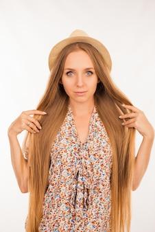 Ritratto di giovane ragazza graziosa che mostra capelli lunghi perfetti