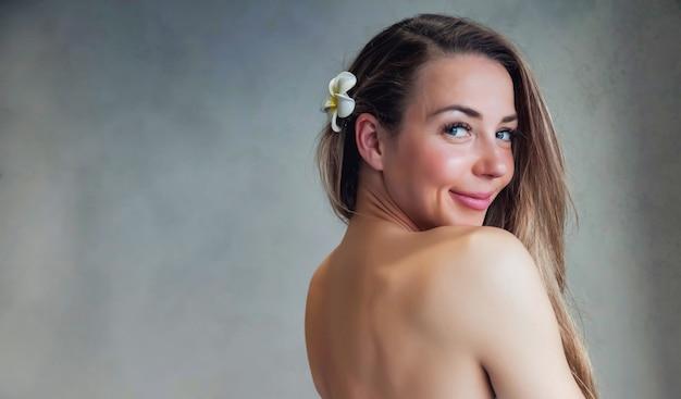 Ritratto di giovane donna piuttosto mezza nuda con fiore per annunci beauty spa o salone di massaggi. ritratto di giovane donna in topless sorridente di mezza età su sfondo grigio. concetto di salute, giovinezza e bellezza
