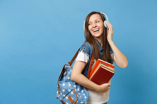 Ritratto di giovane studentessa abbastanza ridente in vestiti di denim con musica d'ascolto delle cuffie dello zaino che tiene i libri di scuola isolati su fondo blu. istruzione al college universitario di scuola superiore.