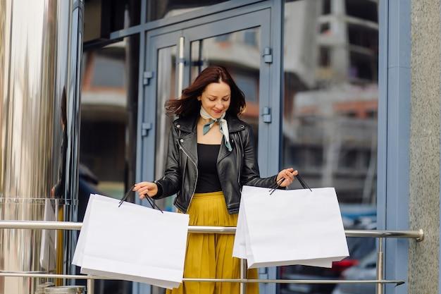 Ritratto di giovane ragazza abbastanza elegante che tiene le borse della spesa e in attesa di buon umore. shopping ideale.
