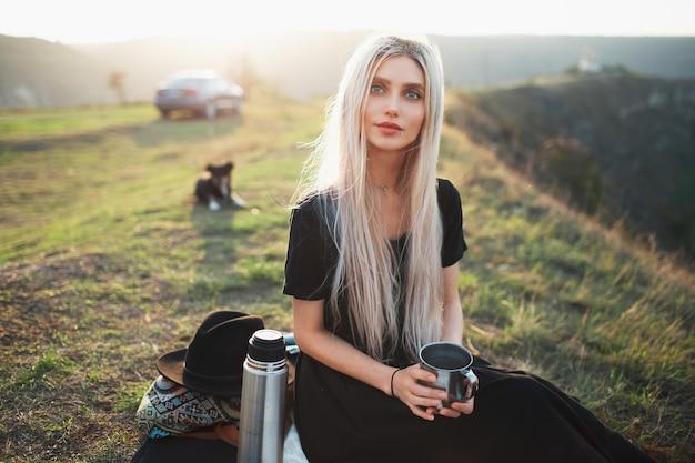 Ritratto di giovane ragazza bionda adolescente graziosa che tiene tazza d'acciaio con tè. sfondo del tramonto.